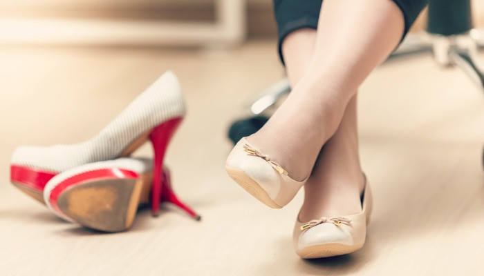 Closeup photo of woman wearing ballet flats instead of high heels